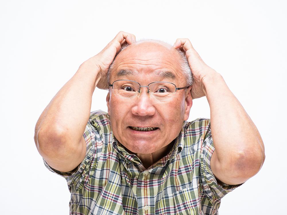 悔しそうに驚く老人の画像